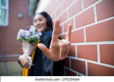 Asian women Wear graduation gown  Raise your finger to show the symbol of love.