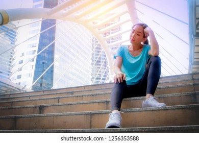 Asian women wear green shirts, sit up tired, and think of something on the stairs, during exercise in the city.