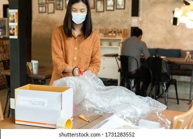 Les femmes asiatiques portent des masques de protection boîte à emballage de colis travaillant en ligne.