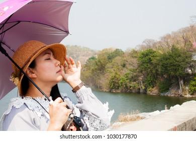 asian women wear umbrella with sunlight rays