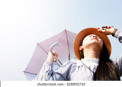 asian women wear umbrella with sunlight rays with over exposure filter