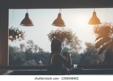 Asian women wear white shirts. She is drinking coffee in the morning garden.Black coffee mug in hand.In the garden there is a girl sitting.Do not focus on objects.