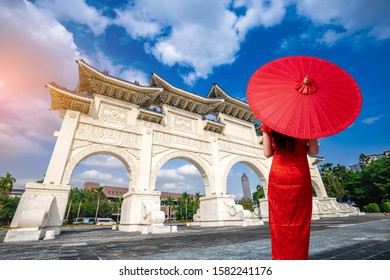 Asian women wearing dresses red cheongsam holding an umbrella visit Gate of Chiang Kai-Shek Memorial Hall ,Taipei, Taiwan