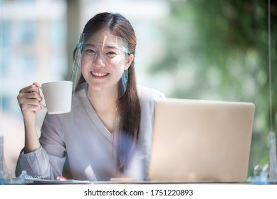Asian women wearing face shield at the coffee cafe, a way to prevent communicable diseases but still be able to lead a new normal life, coronavirus COVID-19 communicable disease prevention