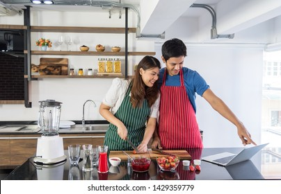 Asian women wearing green aprons is slicing strawberrie and her boyfriend point to the notbook how to do strawberrie smoothie in the kitchen.