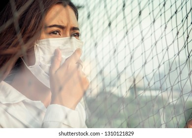 Asian women wearing a mask, the sad eyes looking at the air have the toxic dust 2.5 Particulate Matte enduring against Bangkok pollution crisis .