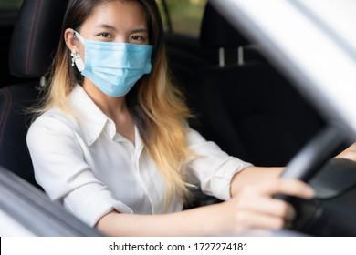 Asian women wearing masks driving