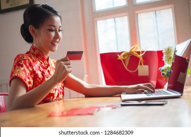 Asian women wearing qipao dresses or red cheongsam are shopping online with a credit card. Happy Chinese New Year Festival.