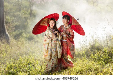 Asian women wearing traditional japanese kimono and red umbrella in the himalayan sakura garden,Thailand.