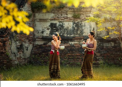 Asian women wearing traditional Thai dress playing water splash in Songkran day, Songkran Festival is the national tradition of Thailand.