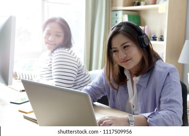 The Asian women working together in the house.