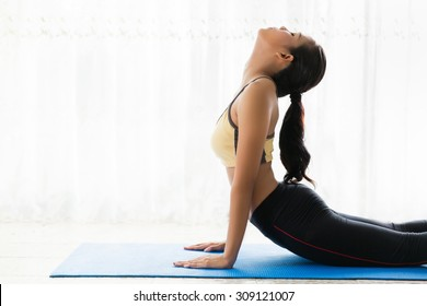 Asian women are yoga exercises at home