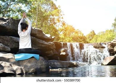 Asian women yoga in nature near waterfall relax time