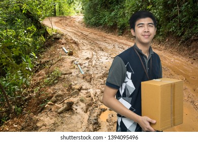 Asian worker carrying box on mud road background, Asian delivery man carrying boxes on mud road background