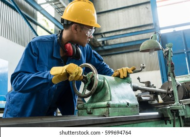 Asian worker checking quality behind an industrial machine indoors in the factory