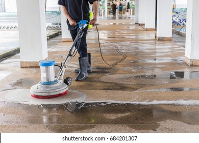 Asian worker cleaning sand wash exterior walkway using polishing machine and chemical or acid