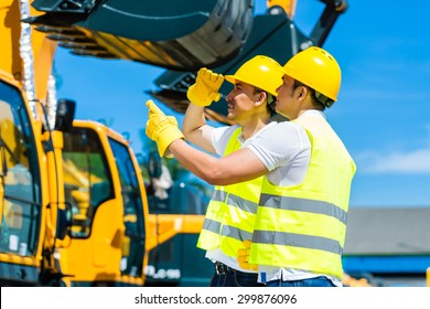 Asian worker at construction machinery of construction site or mining company
