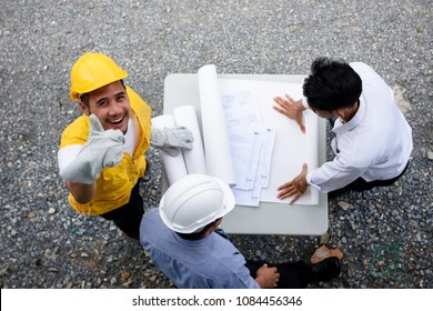 Asian worker froeman thumb up while Engineering team look at paper blueprint plans at construction site. Top view or flat lay portait for teamwork to check project progress.