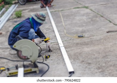 Asian worker with machine cutting metal and welded steel to create a roof, local labor construction concept.