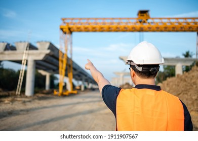 Asian worker man or civil engineer man with protective safety helmet and reflective vest pointing at construction site.