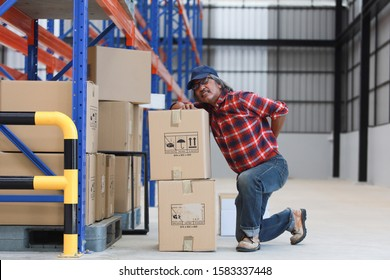 Asian worker man hurt his back lift heavy box in factory
