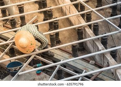 Asian worker on large straw hat remodels timber boardwalk at shore of Singapore sea. Slope-adjustable pedestal used for paver, bearer support instead of bedding sand/brick/concrete/metal pier.