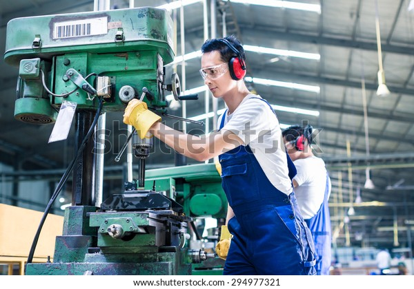Asian worker in production plant drilling at machine on the factory floor