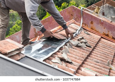 Asian worker replacing roof tiles and metal sheets of old residential building roof