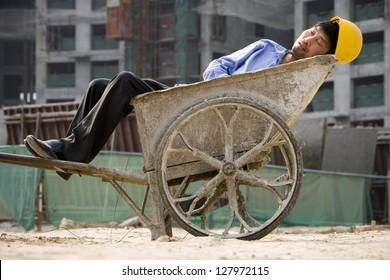 Asian worker sleeping in the wheelbarrow