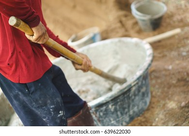 Asian worker using hoe for mixing cement power with sand at small construction site