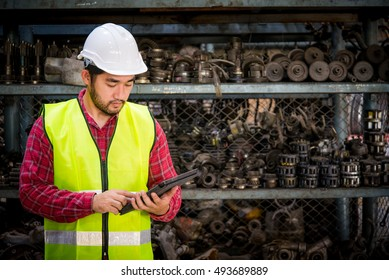 Asian worker using tablet for work in factory warehouse car parts.