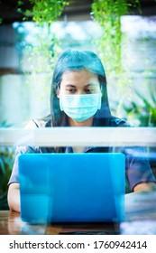 仕事中に自宅で保護マスクを着たアジア人労働者