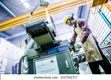 Asian worker wering the goggle, helmet, ear muff equipment in production plant using machine on the factory shop floor