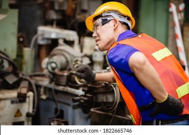 Asiatische Arbeiter, die hart in industriellen Fabriken arbeiten, leiden unter Rückenschmerzen bei der Arbeit an Maschinen.