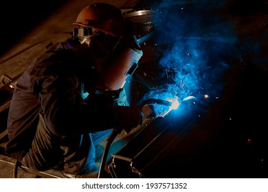 Asian workers are hard welding iron plates in the factory