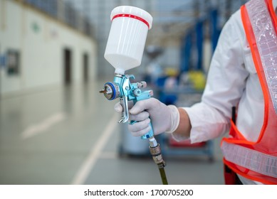 Asian workers stand to hold a spray gun, antiseptic spray gun or car paint gun in protective clothing.