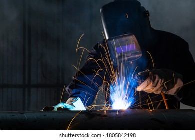 Asian workers wearing safety first uniforms and Welded Iron Mask at Steel welding plants, industrial safety first concept.