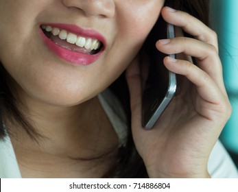 Asian working woman smiling while talking to her friend on her mobile phone at the work place