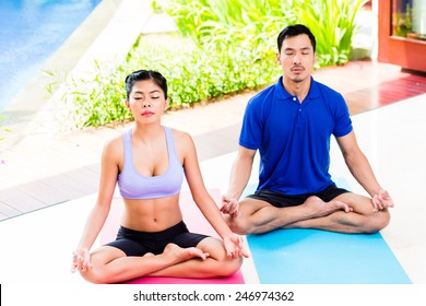 Asian yoga couple in lotus seat mediating in their tropical home in front of garden