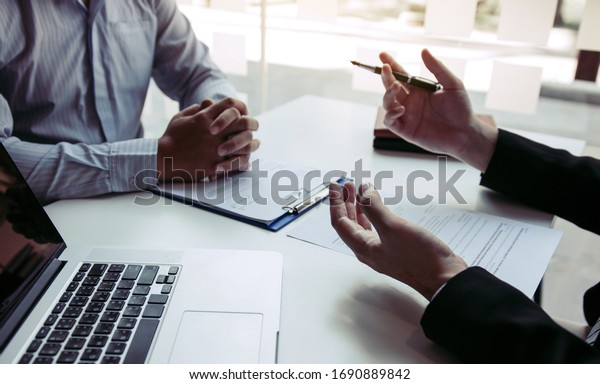 Asian young adult sitting at desk across from manager being interviewed job interview in business room.