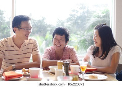 Asian young adults and senior having good time in restaurant