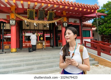 Asian young backpacker found her way by looking at her smartphone. Standing in front of the traditional attraction she is excited and expects to have a cool journey in Naminoue Shrine, Japan.