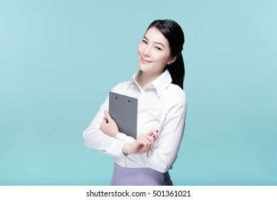 Asian young beautiful business woman in white shirt smiling and cross one's arm with a clipboard, beauty face, tied hair, isolated over blue background.