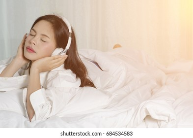 asian young beautiful girl  relaxing and listening to music using headphones, she is lying in bed