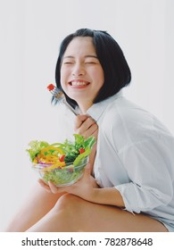 Asian young beautiful woman eating salad with happy mood smile  on white background