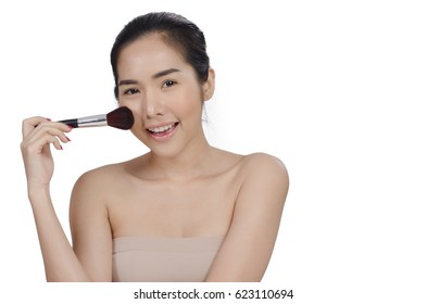 asian young beautiful woman looking and touch her chin with powder brush,natural makeup, skincare, cosmetology and plastic surgery concept