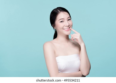 Asian young beautiful woman smiling and pointing at her teeth, natural makeup, beauty face, isolated over blue background.