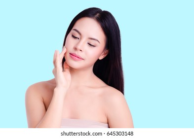 asian young beautiful woman smiling and touching her face, isolated over blue background. natural makeup, SPA therapy, skincare, cosmetology and plastic surgery concept