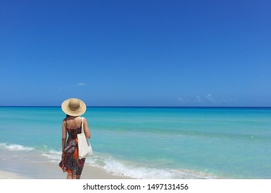 Asian young beautiful women in orange beach dress standing on a beach looking at horizon in Varadero, Cuba Relaxing holiday ocean pictures Beach picture with room for texts Summer vacation