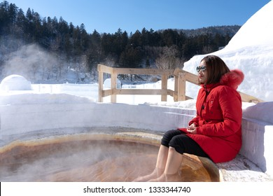 Asian young beauty woman relaxing in hot springs and enjoy the beautiful mountain view with snow in winter.Japanese natural mineral water Onsen at Ice Igloo Village in Lake Shikaribetsu,Hokkaido,Japan